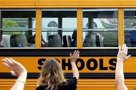 teacher waving to kids on bus